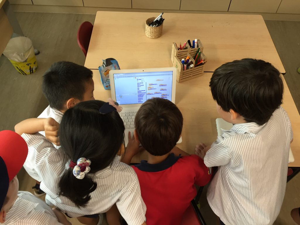 Kids huddled around Scratch laptop